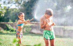 Due childs che giocano nel giardino, si versa dal tubo flessibile, fa una pioggia Immagine felice di concetto di infanzia fotografia stock