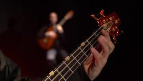 Due chitarristi giocano il basso elettrico Fine in su fiore della sfuocatura della priorità bassa all'interno come gli sguardi s stock footage