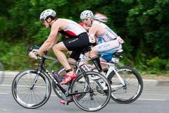Due cicli di velocità di giro dei triathletes durante la concorrenza di triathlon Fotografie Stock