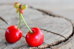 Due ciliege mature rosse isolate su un vecchio fondo di legno con lo spazio della copia per testo closeup Immagini Stock