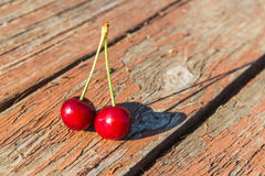 Due ciliege su una tavola di legno Fotografie Stock
