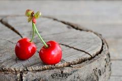 Due ciliegie mature isolate su un vecchio fondo di legno con il posto vuoto per testo Fondo di estate Immagini Stock