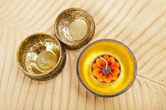 Due ciotole d'ottone e ciotola dorata di legno sul bana marrone immagine stock libera da diritti