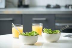 Due ciotole di insalata e di vetri di succo d'arancia Fotografia Stock Libera da Diritti