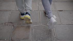 Due cittadini stanno camminando insieme in città nella vista di giorno e posteriore delle loro gambe, vestita nello stile urbano  stock footage