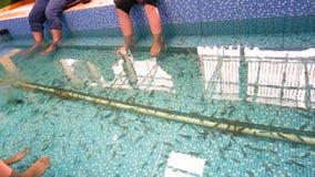 Due clienti che godono della stazione termale del pesce con i piedi sull'acqua fotografie stock