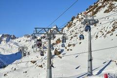 Due collegamenti delle gondole staccabili del mono-cavo con l'alta capacità del trasporto sollevano gli sciatori alla cima della  Fotografia Stock