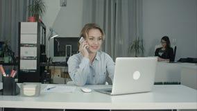 Due colleghe femminili che lavorano le telefonate insieme di risposta nell'ufficio Fotografie Stock Libere da Diritti