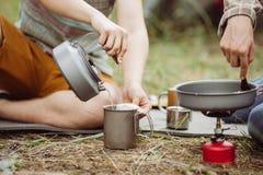 Due colleghi campeggiatori che producono tè e che preparano alimento Fotografia Stock