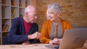Due colleghi caucasici dai capelli grigi senior che collaborano con il computer portatile che è allegro in ufficio stock footage