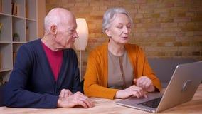 Due colleghi caucasici dai capelli grigi senior che comunicano insieme allegro davanti al computer portatile in ufficio video d archivio