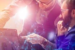 Due colleghi che lavorano alla nuova analisi finanziaria globale di strategia progettano per mezzo del computer portatile Innovaz immagine stock libera da diritti