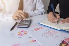 Due colleghi dell'uomo d'affari che discutono piano con i dati finanziari del grafico sulla tavola dell'ufficio con il computer p fotografie stock libere da diritti