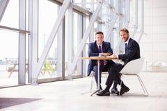 Due colleghi di affari nell'interno moderno, guardante alla macchina fotografica Fotografia Stock Libera da Diritti