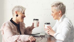 Due colleghi senior femminili che si siedono accanto a ogni altro in un caff? archivi video