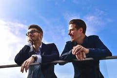 Due colleghi sorridenti che parlano e che si divertono alla via fotografia stock