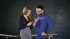 Due colleghi stanno chiacchierando nell'ufficio e stanno dividendo le impressioni circa il loro lavoro L'uomo vestito in camicia  archivi video