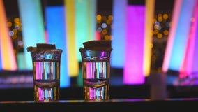 Due colpi d'argento di tequila con calce sul contatore della barra con colore che cambia le lampade principali del tubo video d archivio