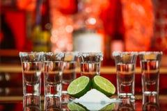 Due colpi della tequila con calce e sale su una barra di legno della tavola sui precedenti delle luci intense della barra Immagine Stock
