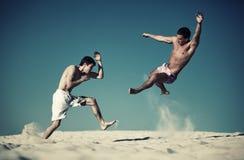 Due combattimenti di sport dei giovani sulla spiaggia Fotografie Stock Libere da Diritti