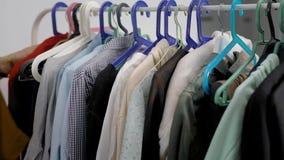 Due compratori di donne sono ganci commoventi e vestiti di scelta in sala d'esposizione, primo piano delle loro mani e barra tras video d archivio