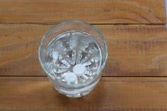 Due compresse in un bicchiere d'acqua si dissolvono fotografia stock libera da diritti