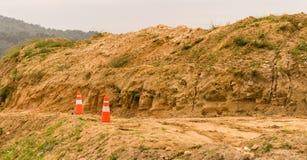 Due coni di traffico che si siedono davanti ad un mucchio di sporcizia Fotografie Stock Libere da Diritti