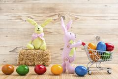 Due coniglietti di pasqua con un carrello e molte uova di Pasqua variopinte Fotografia Stock Libera da Diritti