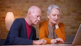Due coniugi caucasici dai capelli grigi senior progressivi che guardano nel computer portatile e che lo discutono nell'ufficio stock footage