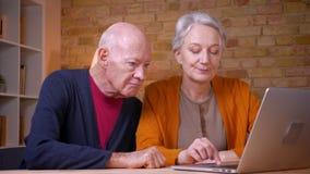 Due coniugi caucasici dai capelli grigi senior progressivi che guardano nel computer portatile che opera una scelta in ufficio archivi video