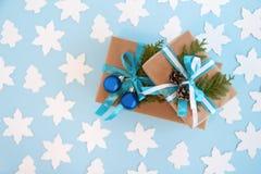Due contenitori di regalo avvolti della carta del mestiere, nastro blu e bianco e rami decorati dell'abete, palle blu di Natale e Immagini Stock