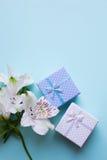 Due contenitori di regalo con alstroemeria fiorisce su backgroun blu-chiaro Fotografia Stock Libera da Diritti