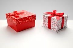 Due contenitori di regalo con i cuori hanno stampato con la cima grigia del fondo Immagini Stock