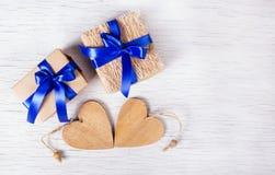 Due contenitori di regalo con i nastri blu e cuori di legno su un fondo bianco Giorno del `s del biglietto di S Copi lo spazio Fotografia Stock