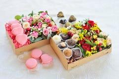 Due contenitori di regalo con il maccherone, il cioccolato ed i fiori Fotografie Stock Libere da Diritti