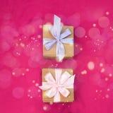 Due contenitori di regalo legati con raso hanno colorato il nastro su un fondo rosa un cuore rosso Immagine Stock