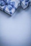 Due contenitori di regalo sul concetto blu di feste del fondo Fotografia Stock