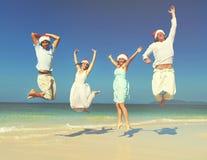 Due coppie che celebrano concetto di estate di Natale della spiaggia Immagini Stock