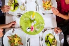 Due coppie multano pranzare nel ristorante Fotografie Stock Libere da Diritti