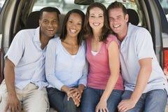 Due coppie che si siedono dentro appoggiano di sorridere del furgone Fotografia Stock
