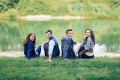 Due coppie che si siedono sull'erba dal fiume hanno girato lo sguardo della macchina fotografica immagine stock libera da diritti