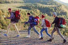 Due coppie felici che camminano nelle montagne con la mappa Giovane uomo caucasico con la mappa che sceglie giusta direzione Cors immagine stock