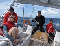 Due coppie i giovani partecipanti alla regata della navigazione stanno guidando nel vento fresco su un yacht di crociera della na fotografie stock