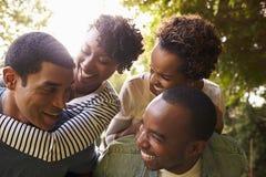 Due coppie nere adulte si divertono trasportando sulle spalle, alto vicino immagini stock libere da diritti