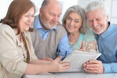Due coppie senior che leggono giornale Immagine Stock Libera da Diritti