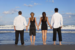 Due coppie, tenenti le mani su una spiaggia Immagine Stock