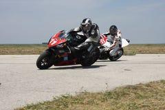 Due corridori della motocicletta alla svolta a sinistra sulla pista Fotografia Stock Libera da Diritti