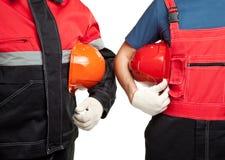 Due costruttori in elmetti protettivi uniformi della holding Fotografie Stock Libere da Diritti