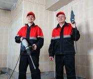 Due costruttori sorridenti in strumenti di holding uniformi Fotografia Stock Libera da Diritti