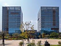 Due costruzioni di affari con esterno di vetro e plaza con gli alberi sul fondo del cielo blu fotografie stock